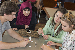Students participate in a team-oriented communication exercise around a LEGO-building activity